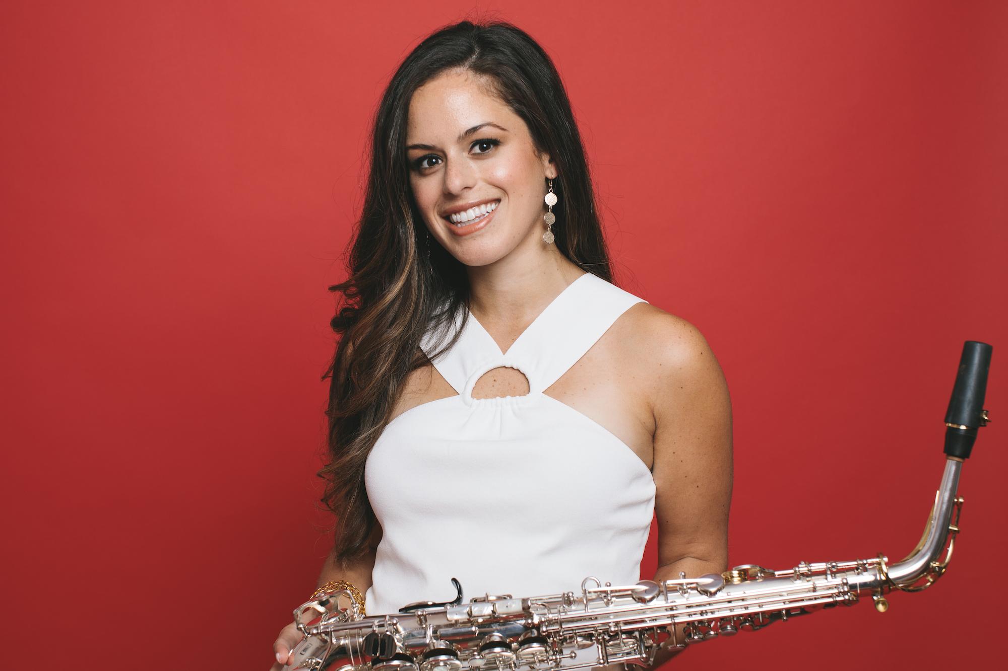Alexa tarantino holding alto saxophone smiling in white dress with orange background
